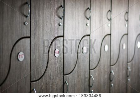 Brown door cells in a wooden checkroom in the gym