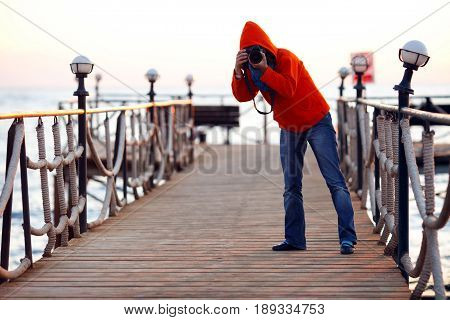 bad spy photographer in a red hoodie hunt for celebrities on the pier