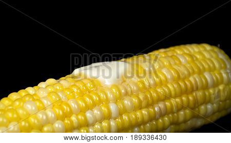 melting butter pat on cooked corn on the cob