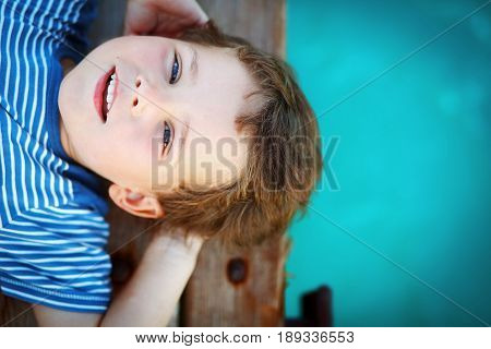 Dream for a whole life. The boy dreams looking to the sky lying on a wooden pier near the water of the turquoise color