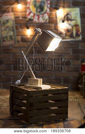 Wooden lamp on an old box in a vintage interior with brick walls