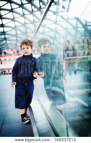 The boy stands on a futurtic bridge reflected in a glass fence