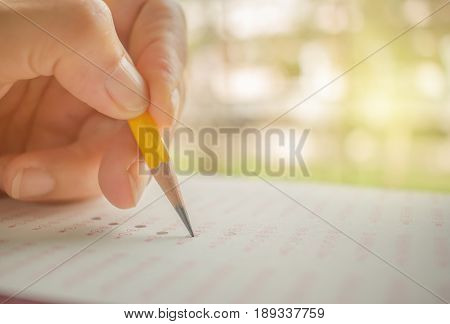 hand student testing in exercise and fill in exam carbon paper computer sheet with yellow pencil education concept
