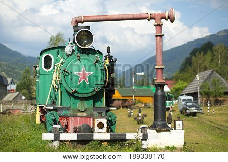 An old rusty locomotive with a red Soviet star stands on an abandoned railway station as a symbol of the collapse of communism