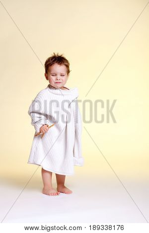 The distressed child in the too big mother's sweater holds the straw in her hands and cries
