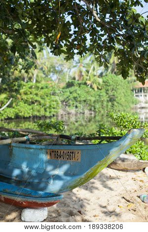 Old wooden blue fishing boat with a float in the shade of tropical trees on a white sandy beach