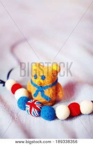 handmade teddy bear and The British flag of fluffy woolen balls is strung like beads on a string