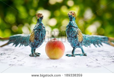 Two ornamental birds covered with copper patina look at a fresh peach