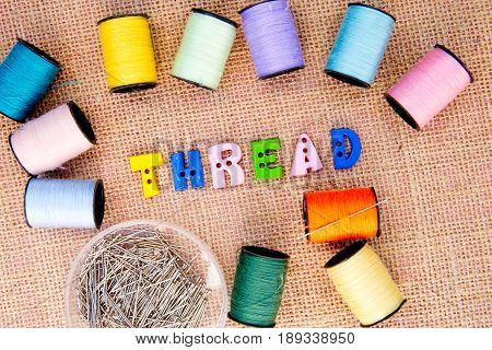 Sewing - Thread spelt in buttons with cotton reels on burlap background