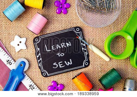 Sewing - Learn to Sew on blackboard with cotton reels, pins, tape measure on burlap background