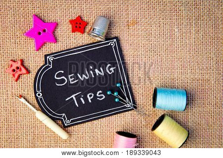 Sewing Tips on blackboard with buttons, cotton thread reels and other items on burlap background
