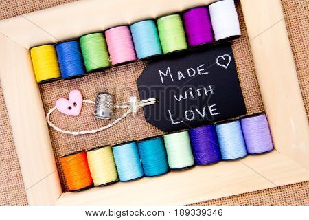 Sewing - Made with Love blackboard with cotton reels in wooden frame with burlap background