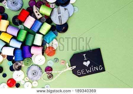 I love Sewing - with blackboard and colorful cotton thread reels on green cardboard background