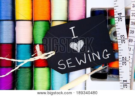 I love Sewing - colorful cotton reels background with blackboard and tape measure and unpicker