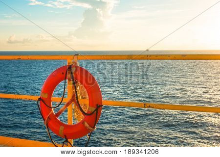 Safety equipment Life buoy or rescue buoy hanging on handrail with sea sky background in sun set time.