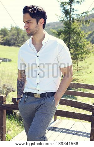 Stylish man with a preppy style posing outdoor