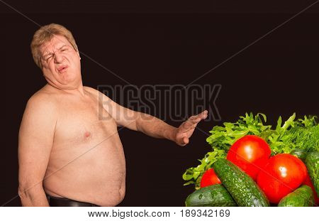The diet concept - overweight and fat man denying healthy food. Collage on black studio background