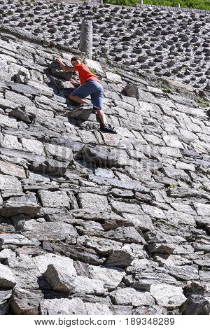 Boy Climbing On The Old Road