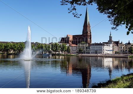 SCHWERIN Germany June 2 2017: Cathedrahle (dome) and a large fountain on the lake pfaffenteich in the capital city of Mecklenburg-Vorpommern tourism destination