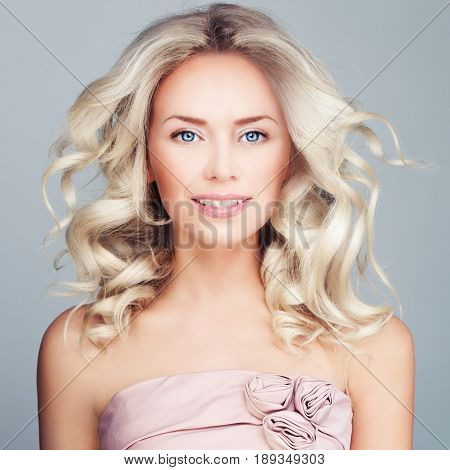 Perfect Blonde Woman with Blowing Blonde Curly Hair and Prom Dress. Fashion Model with Wavy Hairstyle
