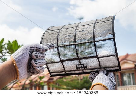 Person Pointing On Thick Dirty Dust On Air Conditioner Filter