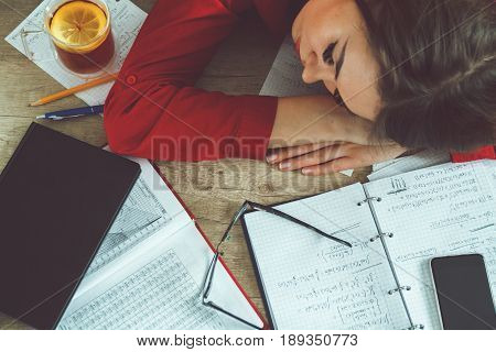 The student girl is tired of doing homework and fell asleep at the table