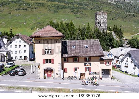 Hospital, Switzerland - 7 August 2016: cyclists pedaling on the old road which leads to St. Gotthard pass at the village of Hospental on the Swiss alps