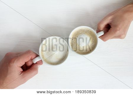 Two cups with frothy cappuccino in hands/ coffee break in a top view