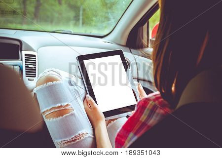 Girl with tablet in her hands in the car. Hitchhiking, car ride concept