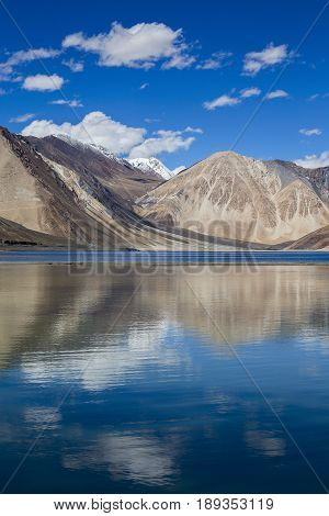 Sunny day at Pangong Lake water and Himalayan mountain in India. Pangong Lake is an endorheic lake in the Himalayas situated at a height of about 4350 m in Ladakh India. It is 134 km long from India to Tibet