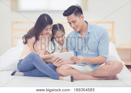 Happy Family In The Bedroom,asian Father And Mother Watching Cartoon With Daughter On Smart Tablet T