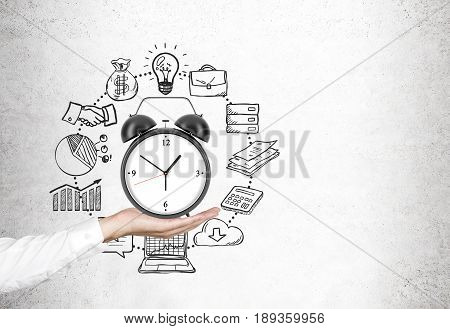 Close up of a hand of a businessman in a white shirt holding an alarm clock. Concrete background with time management icons. Mock up