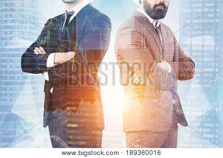 Close up of two unrecognisable businessmen standing with crossed arms against a skyscraper with graphs in the background. Toned image double exposure