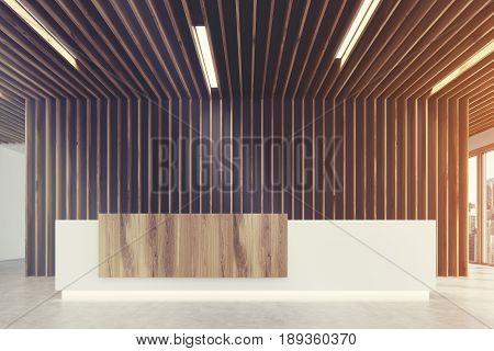 Close up of a white and light wooden reception counter is standing in a light colored office lobby with wooden decoration elements. Panoramic window. Empty hall. 3d rendering mock up toned image