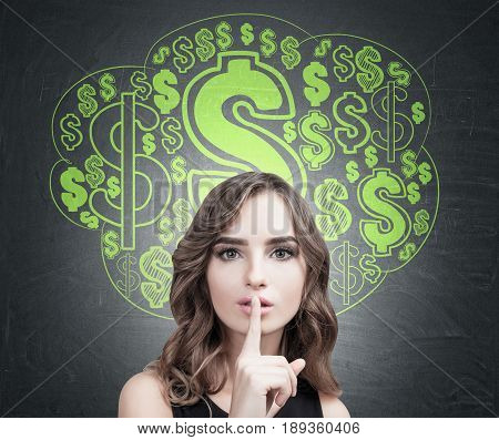 Close up of a young European woman with wavy hair making a hush sign. Blackboard background with a green dollar sign cloud sketch on it.