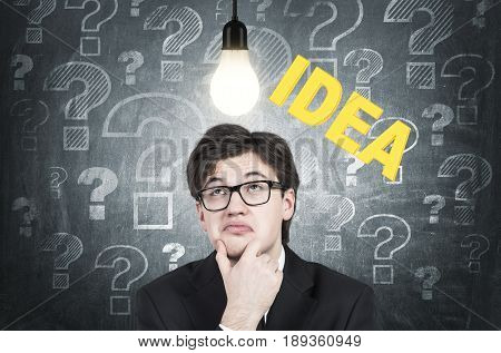 Close up of a skeptical young businessman with wavy hair wearing glasses standing near a blackboard with question marks on it and a light bulb hanging on its wire above man s head.
