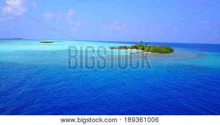 Aerial flying drone view of Maldives white sandy beach on sunny tropical paradise island with aqua blue sky sea water ocean 4k