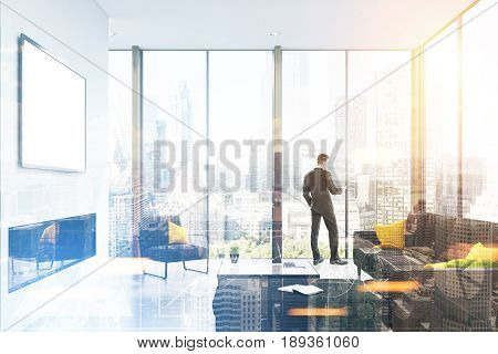 Rear view of a businessman standing near a panoramic living room window and looking at his smartphone screen. A gray sofa and a large coffee table. 3d rendering mock up toned image double exposure