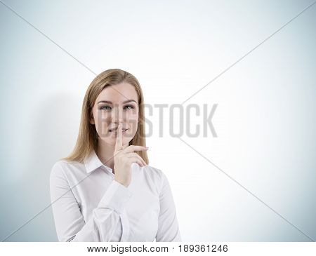 Portrait of a blond businesswoman wearing a white shirt and making a hush sign. Concept of conspiracy and keeping a secret. Gray wall background. Mock up