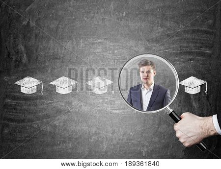 Close up of a big boss s hand with a magnifying glass picking the right candidate for the job. Man s portrait in a row of graduation hats.
