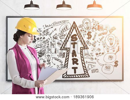 Side view of a young woman in a yellow hardhat reading a document attached to a clipboard standing near a whiteboard with a startup arrow. Toned image.