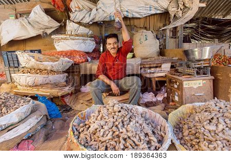 BANGALORE, INDIA - FEB 16, 2017: Happy indian trader of vegetables and ginger selling vegetables to customers on February 16, 2017. With population 8.52 million Bangalore is 3rd most populous indian city