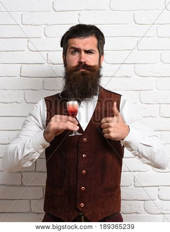handsome bearded man with long beard and mustache has stylish hair on serious face holding glass of alcoholic shot in vintage suede leather waistcoat on white brick wall studio background