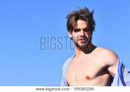 Bearded man short beard. Caucasian macho with moustache and ruffled hair in blue striped pajamas showing strong chest on torso on blue sunny sky background