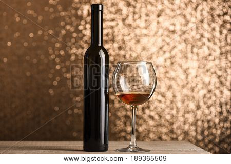 Glass With Brown Beverage Near Wine Bottle On Wooden Surface
