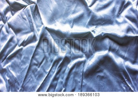 blue atlas silk creased cloth material as background texture composition