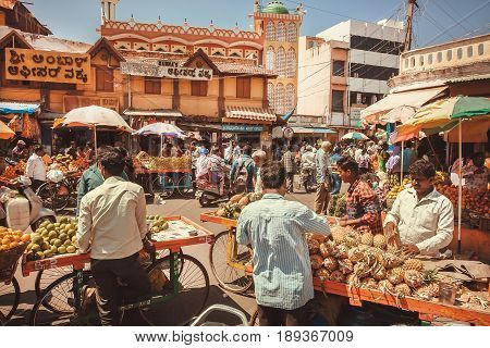MYSORE, INDIA - FEB 16, 2017: Traders of pineapples and tropical fruits talking with customers at street market on February 16, 2017. With population 900000 Mysore is the cultural capital of Karnataka