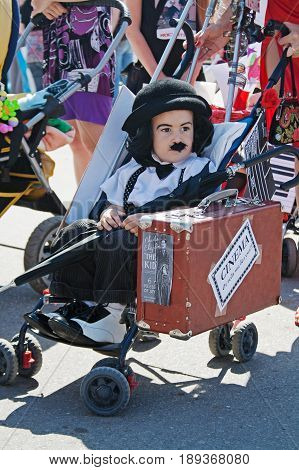 Volgograd Russia - May 29 2010: Child looking like a Charlie Chaplin in hat and with umbrella and suitcase sitting in the stroller in the parade of prams in Volgograd