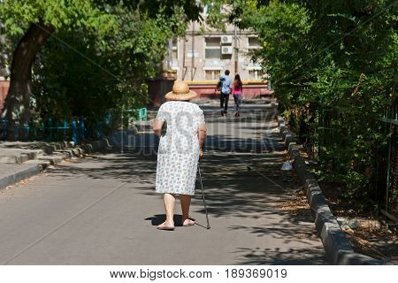 Senior woman in hat and with a cane walking down the street after for a couple in summertime