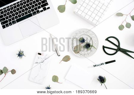 Flat lay home office desk workspace with laptop mobile phone with marble case pen paper notebook and eucalyptus branches on white background. Top view.